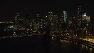 AX67_0081 - Aerial stock footage of 4K stock video aerial view approach the Brooklyn Bridge and Lower Manhattan skyline at night, New York