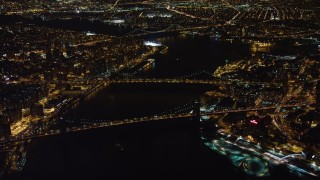AX67_0096 - Aerial stock footage of 4K stock video aerial view of approaching Brooklyn Bridge, Manhattan Bridge at night, New York