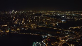 AX67_0100 - Aerial stock footage of 4K stock video aerial view of flying by Brooklyn Bridge, Manhattan Bridge at night, New York