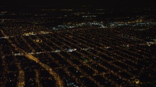 AX67_0112 - Aerial stock footage of 4K stock video aerial view of passing urban neighborhoods in Queens at night, New York