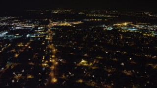 AX67_0120 - Aerial stock footage of 4K stock video aerial view follow Hempstead Turnpike to reveal and approach Republic Airport at night, Long Island, New York