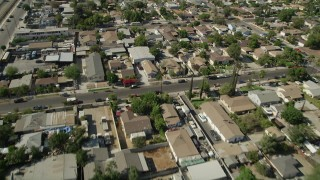 AX68_001 - 5K stock footage aerial video reverse view of urban neighborhoods, revealing warehouse buildings in Pacoima, California