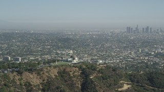 AX68_004 - 5K stock footage aerial video Griffith Observatory with a view of Downtown Los Angeles skyline, California