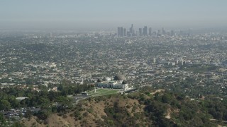 AX68_005 - 5K stock footage aerial video pass by Griffith Observatory with Downtown Los Angeles in the distance, California