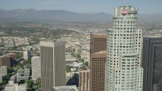 AX68_024 - 5K stock footage aerial video approach the top of US Bank Tower in Downtown Los Angeles, California, and reveal City Hall