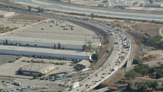 AX68_035 - 5K stock footage aerial video approach heavy freeway traffic by warehouse buildings in Vernon, Los Angeles, California