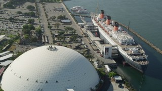 AX68_068 - 5K stock footage aerial video reverse view of the Queen Mary luxury liner and reveal Downtown Long Beach, California