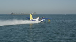 AX68_077 - 5K stock footage aerial video track a seaplane taking off from San Pedro Bay in Long Beach, California