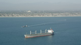 AX68_082 - 5K stock footage aerial video of a barge sailing near an oil tanker in San Pedro Bay near the coast, Long Beach, California