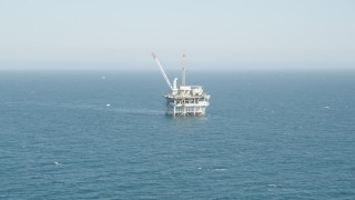 AX68_088 - 5K stock footage aerial video tilt to reveal and approach an offshore oil platform near Long Beach, California