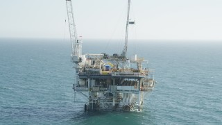 AX68_090 - 5K stock footage aerial video orbit an oceanic oil platform near Long Beach, California