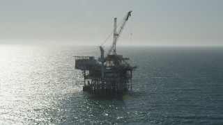 AX68_091 - 5K stock footage aerial video of orbiting around the side of an oceanic oil platform near Long Beach, California