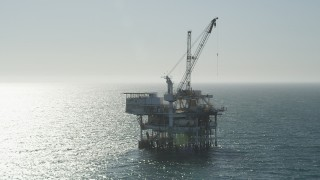 AX68_092 - 5K stock footage aerial video orbit an oceanic oil drilling platform near Long Beach, California