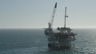 AX68_094 - 5K stock footage aerial video orbit oceanic oil derrick near Long Beach, California