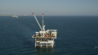 AX68_097 - 5K stock footage aerial video orbit of an oceanic oil platform with Long Beach in the background, California