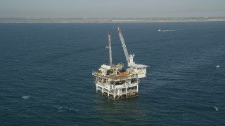 AX68_098 - 5K stock footage aerial video of an orbit of an oceanic oil platform near the California Coast, Long Beach