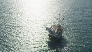 AX68_101 - 5K stock footage aerial video orbit of an oil platform off the coast of California near Long Beach