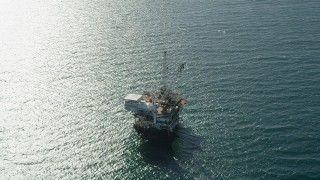 AX68_107 - 5K stock footage aerial video of an oil drilling platform near sunlight reflected off the ocean near Long Beach, California