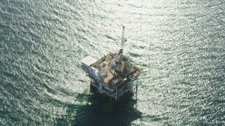 AX68_108 - 5K stock footage aerial video of tilt to a bird's eye view of an oil derrick near Long Beach, California
