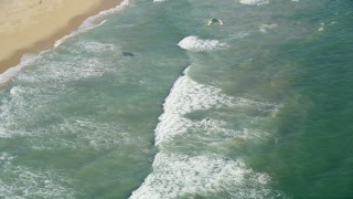 AX68_120 - 5K stock footage aerial video reverse view of a kite surfer in San Pedro Bay by the beach, Long Beach, California