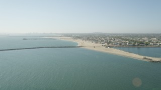 AX68_121 - 5K stock footage aerial video approach the breakwater, pier, beach and coastal neighborhoods in Seal Beach, California