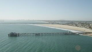 AX68_123 - 5K stock footage aerial video of Seal Beach Municipal Pier and the beach by coastal homes in Seal Beach, California