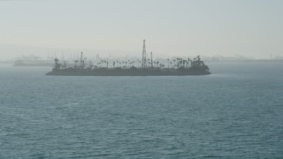 AX68_125 - 5K stock footage aerial video tilt from San Pedro Bay to reveal Island Chaffee oil island, Long Beach, California