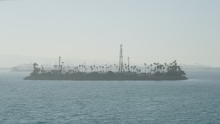 AX68_126 - 5K stock footage aerial video approach the oil drilling Island Chaffee in San Pedro Bay, Long Beach, California