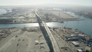 AX68_140 - 5K stock footage aerial video follow light I-710 traffic to the Gerald Desmond Bridge at the Port of Long Beach, California