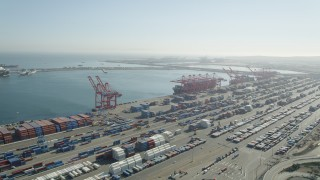 AX68_142 - 5K stock footage aerial video of cargo containers and ships under cranes at the Port of Long Beach, California