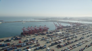 AX68_143 - 5K stock footage aerial video of cargo ships under cranes near containers at the Port of Long Beach, California