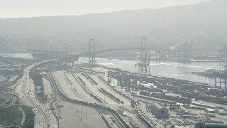 AX68_144 - 5K stock footage aerial video approach train yard and Vincent Thomas Bridge at the Port of Los Angeles, California
