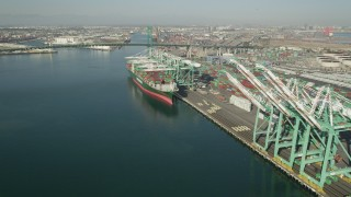 AX68_162 - 5K stock footage aerial video approach a cargo ship beneath cranes at Port of Los Angeles, California