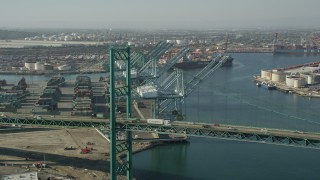 AX68_164 - 5K stock footage aerial video fly over Vincent Thomas Bridge to approach cranes at the Port of Los Angeles, California