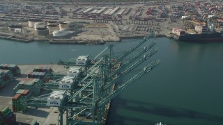 AX68_166 - 5K stock footage aerial video fly over cargo cranes and pan to a ship docked at the Port of Los Angeles, California