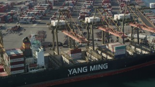 AX68_168 - 5K stock footage aerial video of cranes working over a cargo ship at the Port of Los Angeles, California