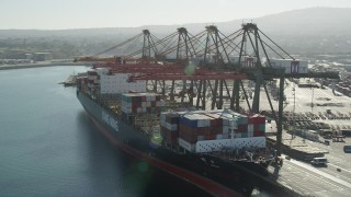 AX68_169 - 5K stock footage aerial video orbit cranes unloading a cargo ship at the Port of Los Angeles, California