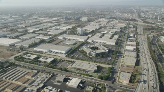 AX68_181 - 5K stock footage aerial video of office buildings and several warehouses by I-110 in Torrance, California