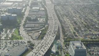 AX68_184 - 5K stock footage aerial video of heavy traffic on I-405 between office buildings and homes in Torrance, California