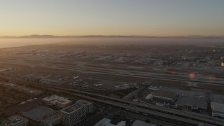 AX69_005 - 5K stock footage aerial video of sunset at LAX with an airliner on a runway in Los Angeles, California