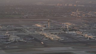 AX69_008 - 5K stock footage aerial video of LAX control tower and terminals as airliner lands at sunset, Los Angeles, California