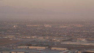 AX69_010 - 5K stock footage aerial video track an airliner on approach to LAX at sunset, Los Angeles, California