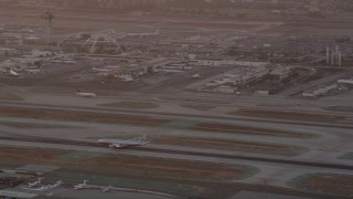 AX69_012 - 5K stock footage aerial video track airliner on runway and tilt to reveal control tower and terminals at LAX at twilight, Los Angeles, California