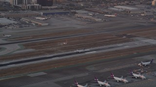 AX69_014 - 5K stock footage aerial video track passenger jet landing on runway at sunset at LAX, Los Angeles, California