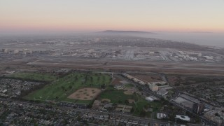 AX69_018 - 5K stock footage aerial video pan across Los Angeles International Airport at sunset in California