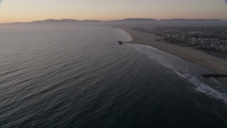 AX69_025 - 5K stock footage aerial video tilt to reveal Venice Fishing Pier and empty beach to Santa Monica at sunset, California