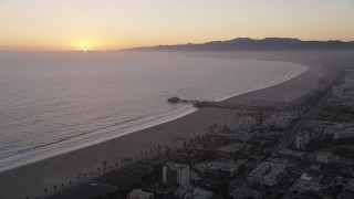 AX69_030 - 5K stock footage aerial video of the Santa Monica Pier with the sun setting in the horizon, California
