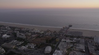 AX69_038 - 5K stock footage aerial video flyby beachside buildings and Santa Monica Pier at twilight, California