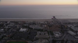 AX69_039 - 5K stock footage aerial video orbit buildings by the beach and Santa Monica Pier at twilight, California