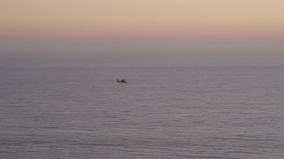 AX69_044 - 5K stock footage aerial video track a Coast Guard helicopter flying over the Pacific Ocean at twilight